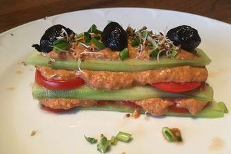 Lasagnes alternant tranches de concombre, tranches de tomates, sauce au poivron, décorée avec des graines germées et des olives noires
