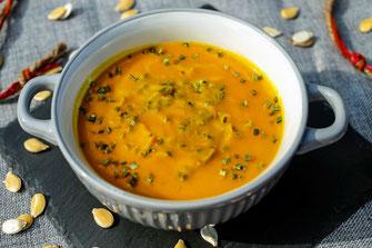 Bol de soupe à la butternut parsemée de paillettes de coriandre