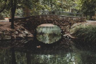 Einsame alte Steinbrücke über den Teich im Park