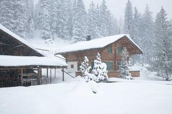 Verschneites Holzhaus oder Hotel im Wald bei Kandersteg am Oeschinensee