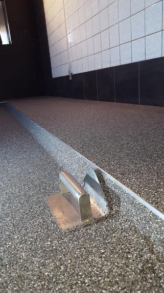 Troffelvloer met opstaande sanitairplint in een horecakeuken