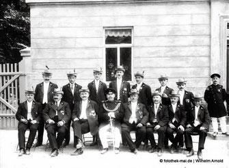 Männergruppe vor Gebäude mit Hüten