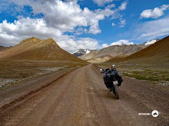 Motorrad KTM 690. Tadschikistan, Passstrasse, Schotter, Berge, blauer Himmel mit weissen Wolken