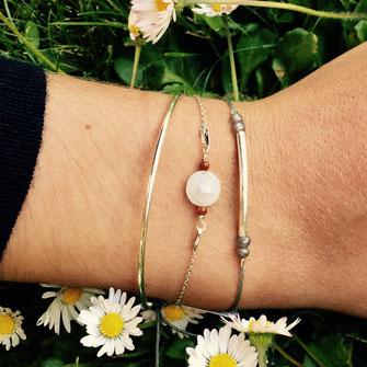 Superposition de bracelets sur poignet : un jonc doré à l'or fin, un tube en argent 925 doré jaune suivi d'une pierre de lune entourée de petites perles de verre rouge sur chaîne en plaqué or jaune.