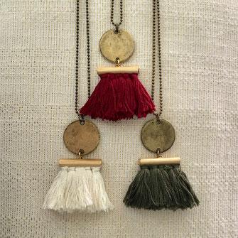Sautoirs composés d'un pompon fait main en coton ivoire, kaki ou framboise, suspendu à un sequin en étain, le tout sur une chaîne à billes en laiton bronze