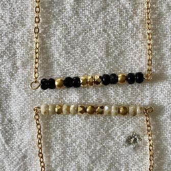 Colliers composés d'un rang de petites perles facettées ivoire et doré, ou noires et dorées sur chaîne dorée à l'or fin