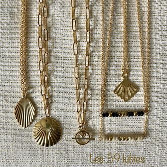 Des breloques dorées à l'or fin, des petites perles facettées dorées ivoires et noires montées sur des chaînes à maillons ovales et sur chaîne forçat aplatie