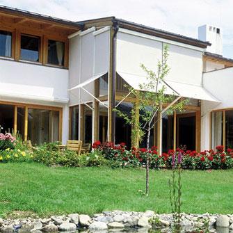 Helle Fassadenmarkisen auf den Fenstern eines Hauses mit großem Garten