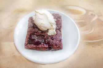 Brownie auf weissem Teller, dekoriert mit Sahne