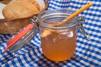 Quittengelee im Einweckglas mit gelbem Löffel auf blau-weiss karierter Tischdecke