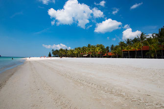 Weisser Sand und weitlaufiger Strand mit Palmen und Bungalows auf Langkawi Cenang