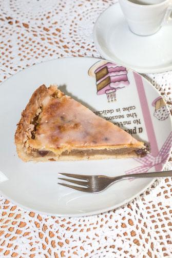 Ein Stück gedeckter Apfelkuchen auf Dessertteller mit Kuchengabel auf weisser Tischdecke-hochkant