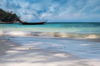 Seichte Wellen und Boot am Haad Salad Beach auf Koh Phangan