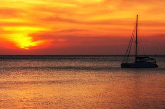 Goldener Sonnenuntergang mit Segelschiff über der Andamanensee auf Ko Lanta