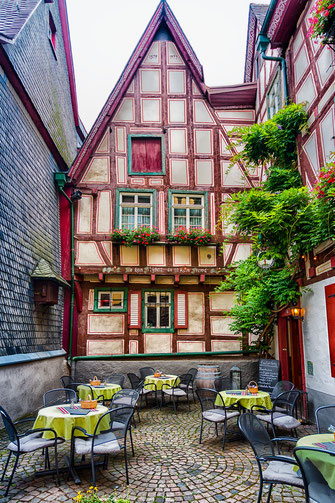 Restaurant - Tische und Stühle inmitten von Fachwerkhausern in der Altstadt von Bacharach am Rhein