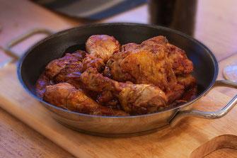 Pollo alla Cacciatora - Huhn nach Jägerart in einer Pfanne serviert