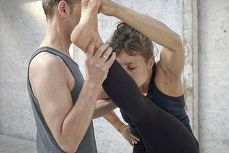 Der Yogalehrer gibt beim Unterrichten sogenannte Adjustments oder Assists.