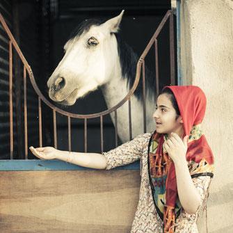 National Geographic: Iran – Tausend und ein Widerspruch. Porträt Mädchen moderne Kleidung Hedjab mit Pferd