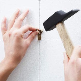 Accrocher un clou avec un marteau