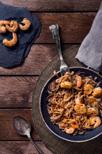 Riesen Gambas Low Carb Pasta in Pfanne auf rustikalem Holztisch von Tobias Gawrisch Xplor Creativity