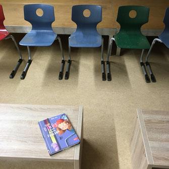 Zuschauerbänke, Bücher, Tisch für Lesung in einer Bücherei