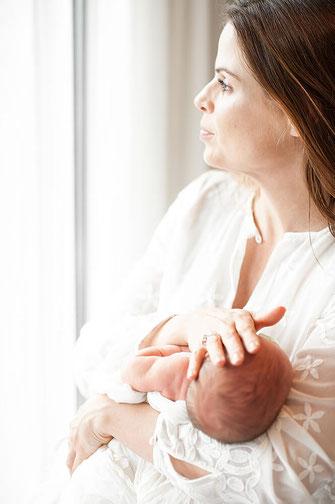 Helles whitestyle Newborn Fotoshooting Mutter hält Kind und schaut aus dem Fenster fotografiert von der Schweizer Familien Fotografin Monkeyjolie