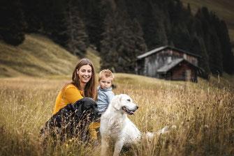 Labrador und golden Retriever und Frau mit Kind auf einer Blumenwiese in der Schweiz festgehalten von der Familien Fotografin Monkeyjolie