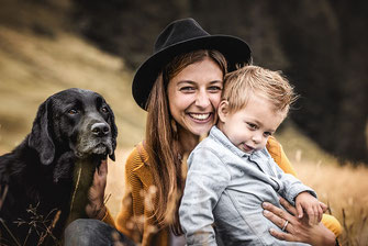 Frau mit Labrador und Fedora Hut und Kind auf einer Blumenwiese in der Schweiz festgehalten von der Familien Fotografin Monkeyjolie