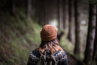 Ein Mädchen mit Norweger Pulli und Beanie im Wald von hinten fotografiert festgehalten von der Abenteuer Fotografin Monkeyjolie in Graubünden
