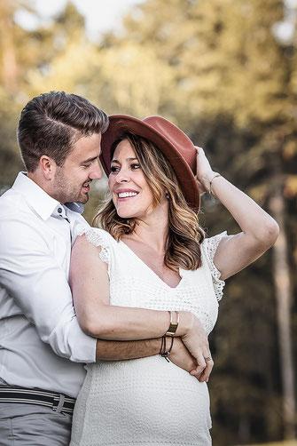 Schwangerschafts Shooting mit einem Ultraschallbild, sie trägt ein Sommerkleid und einen Hut er hält sie und den Babybauch fest fotografiert von der Familien Fotografin Monkeyjolie