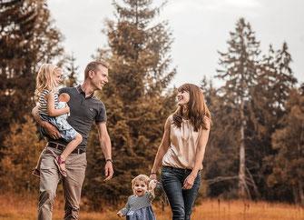 Lachende Familie mit Eltern und zwei Kindernlaufen durch eine Moorlandschaft im Hintergrund ein Wald festgehalten von der Familien Fotografin Monkeyjolie