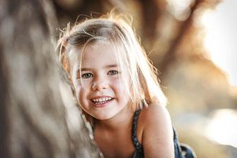Freches Mädchen schaut um einen Baumstamm herum in die Kamera und lächelt im Hintergrund ein Sonnenuntergang festgehalten von der Familien Fotografin Monkeyjolie