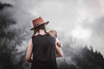 Mutter mit einem Fedora im Bohemien Style hält Ihr Kind im Arm und schaut in die Berge fotografiert von der Familien Fotografin Monkeyjolie in der Ostschweiz