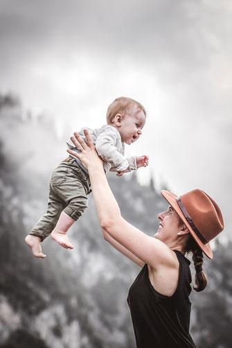 Mutter hält Ihr Kind hoch und lacht dabei vor einer Berg Kulisse mit Tannen und Nebel fotografiert von der Ostschweizer Familien Monkeyjolie