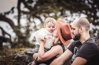 Mutter und Vater mit Ihrem Kind am Lagerfeuer im Bohemien Style sie küsst Ihr Kind fotografiert von der Familien Fotografin Monkeyjolie in der Ostschweiz