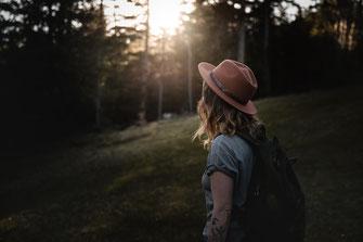 Mädchen mit Bohemien Fedora Hut steht auf einer Alpenwiese man sieht nur Ihr Profil im Hintergrund ein Sonnenuntergang der duprh die Tannen scheint festgehalten von der Abenteuer Fotografin Monkeyjolie in Graubünden