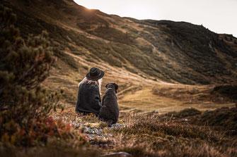 Schoko Labrador schaut auf die Berglandschaft sitzt neben seiner Besitzerin fotografiert von der Ostschweizer Hunde Fotografin Monkeyjolie