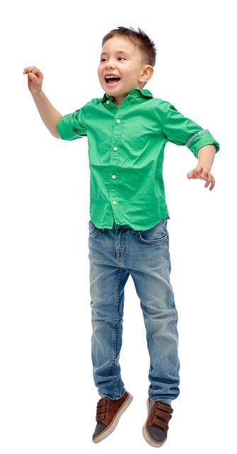 Kind springt und ist glücklich weil es in Geldern zur Schule geht