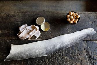 Cuir de saumon disposé à coté d'un bol rempli de noix de galle, d'un chiffon et d'une boîte de cirage