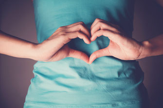 Eine Frau formt aus ihren Händen ein Herz vor dem Bauch