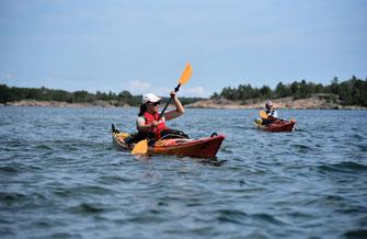 KompassNord in Schweden in Kajaks unterwegs. Mehrere Boote auf dem Wasser bei herrlichem Sonnenschein und kleinen Inseln.