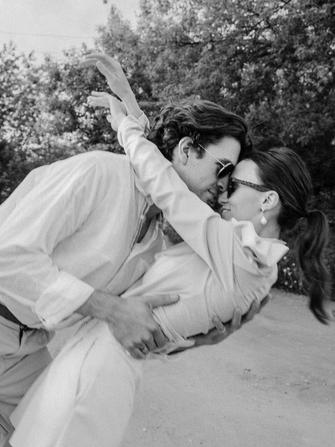 Glücklich kuschelndes Pärchen. Chic trifft Cool: Sonnenbrille und Perlenohringe. Mini-Hochzeiten Angebot für Covid Braut Concierge