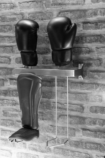 stainless shin guard rack with gloves bolted to a brick wal