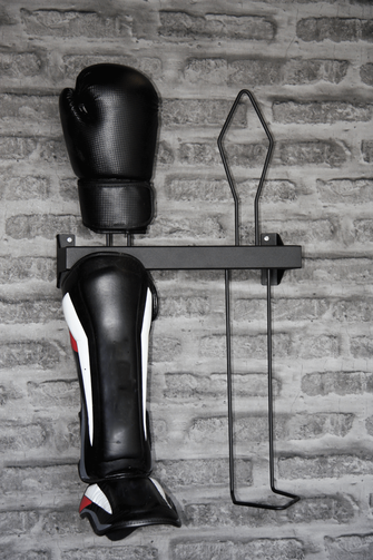 black shin guard rack with a single glove bolted to a brick wall