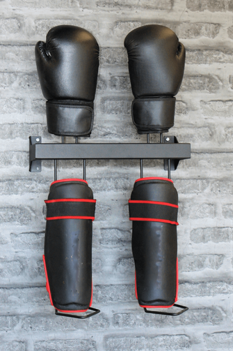 black shin  and  glove guard rack bolted to a brick wall