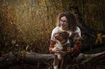 Mädchen mit dunklen Locken hält Ihren Welpen im Arm in der Natur fotografiert von der Familien Fotografin Monkeyjolie in der Ostschweiz