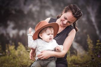 Mutter mit einem kleinen Jungen hält Ihr Kind im Arm und schaut in die Berge fotografiert von der Familien Fotografin Monkeyjolie in der Ostschweiz