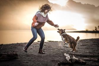 Mädchen spielt mit Ihrem Aussie Welpen am Sand Strand sie hält ihren Aussie Welpen im Arm fotografiert von der Familien Fotografin Monkeyjolie in der Ostschweiz