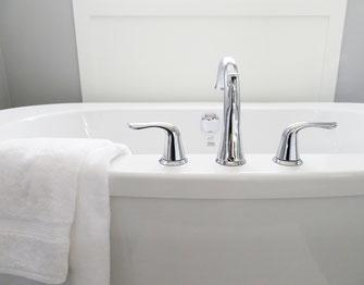 Weiße Badewanne mit Wasserhähnen und Handtuch
