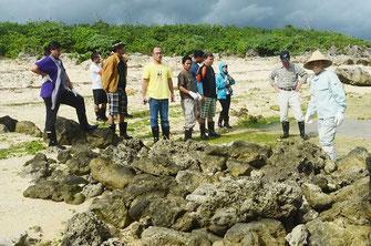 大泊さんと山城さんの指導で、魚垣の補修を体験した研修生ら=白保海岸